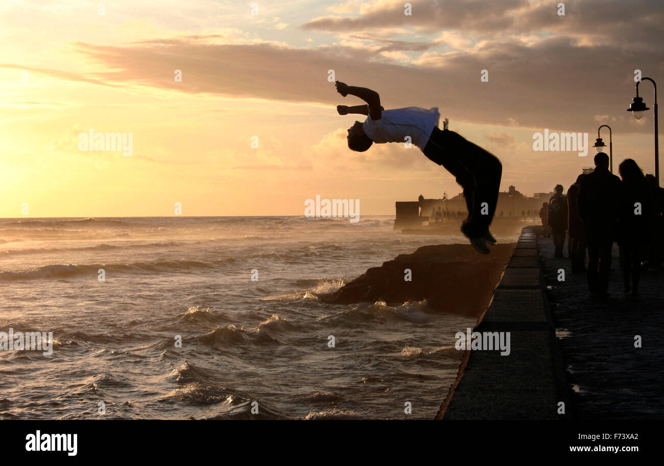 Parkour performer jumping while people walk along the stony boardwalk of Cadiz, Spain - Stock Image