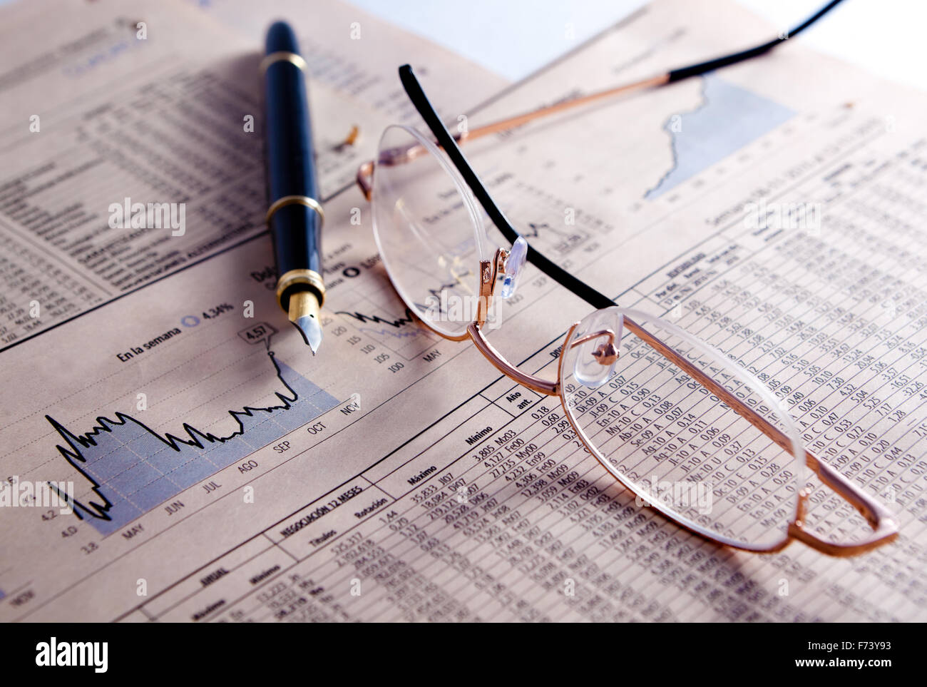 Financial and statistical background with graphics,glasses and pen - Stock Image