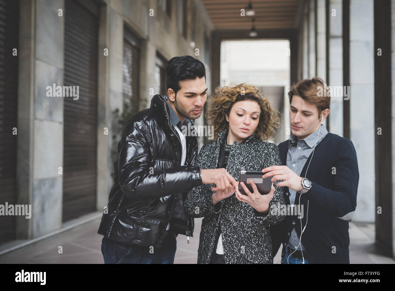 Half length of multiracial business people working outdoor in town using a tablet, all of them looking downward - Stock Image