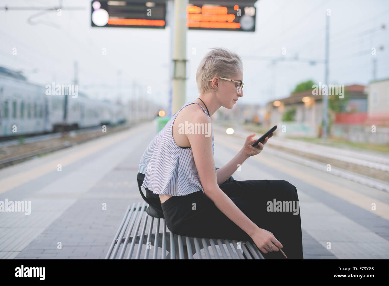 young handsome caucasian blonde italian designer sitting on a bench in railway station, using smartphone and smoking, - Stock Image