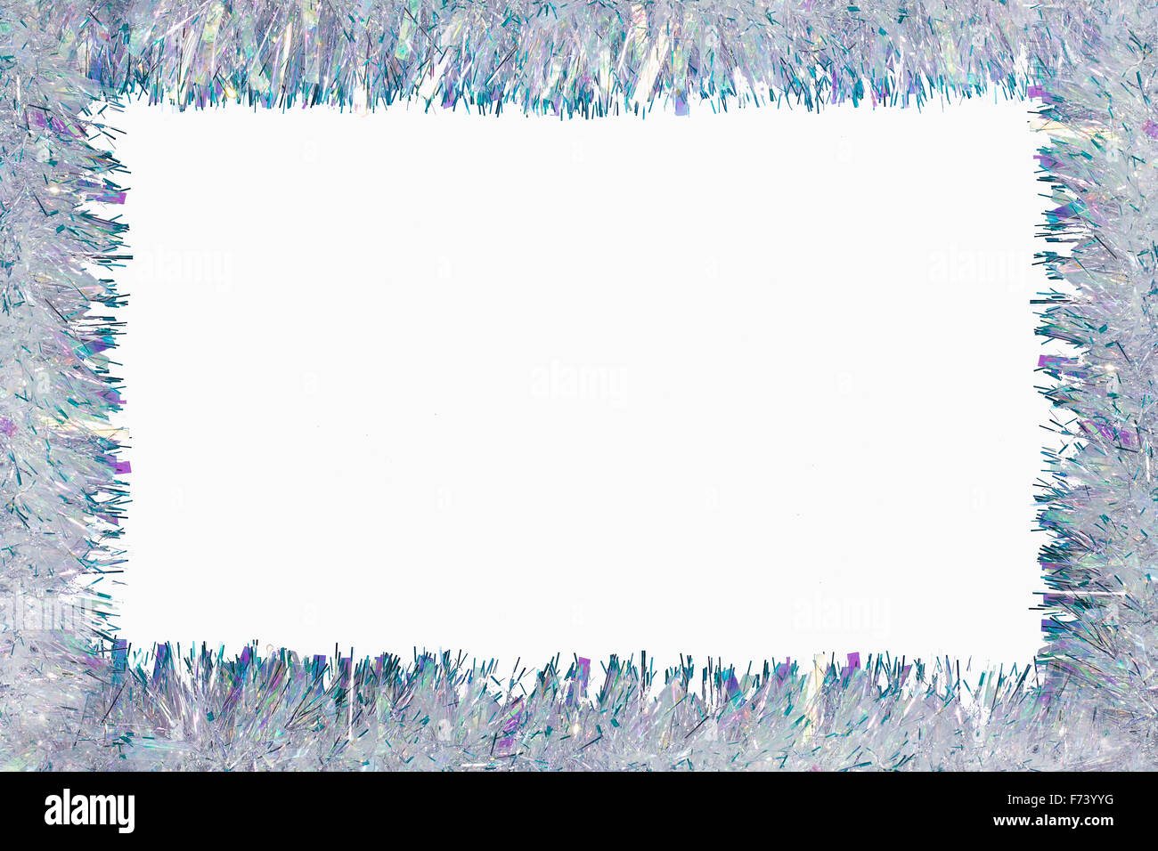 Christmas frame of tinsel garland isolated on white - Stock Image