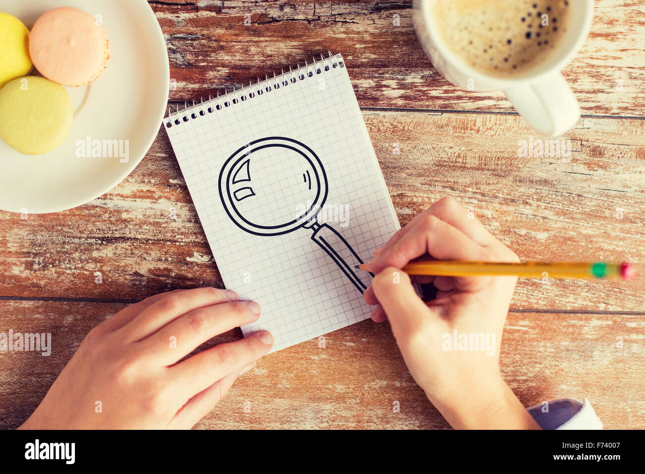 close up of hands drawing magnifier in notebook - Stock Photo