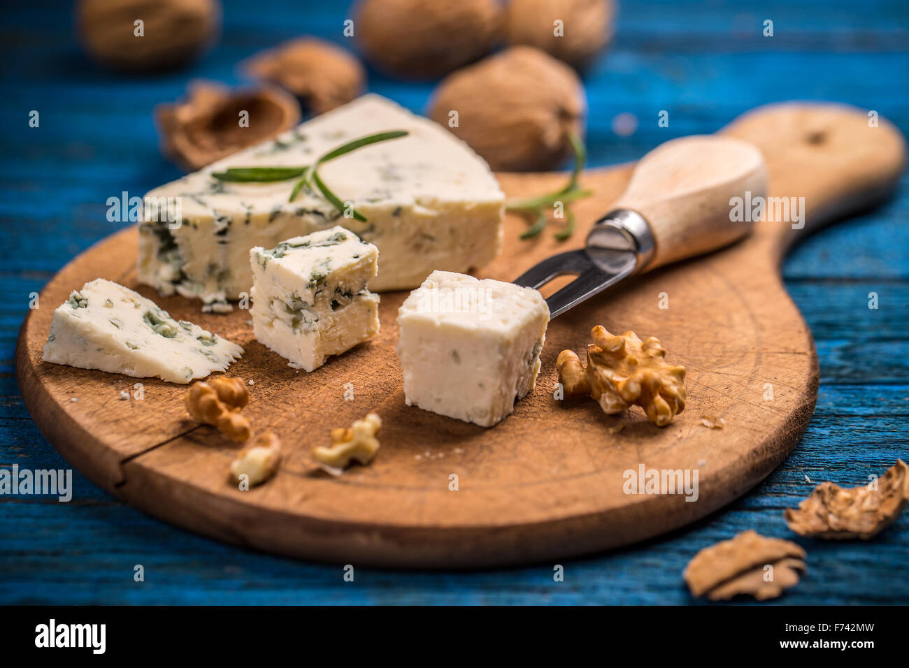 Cheese with mold on wooden cutting board - Stock Image
