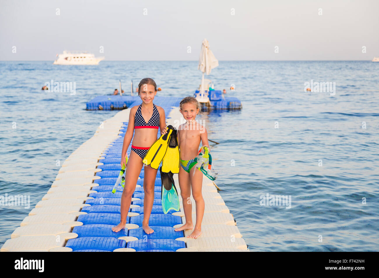 Cute girls with water masks and swim fins walking on pontoon Stock Photo