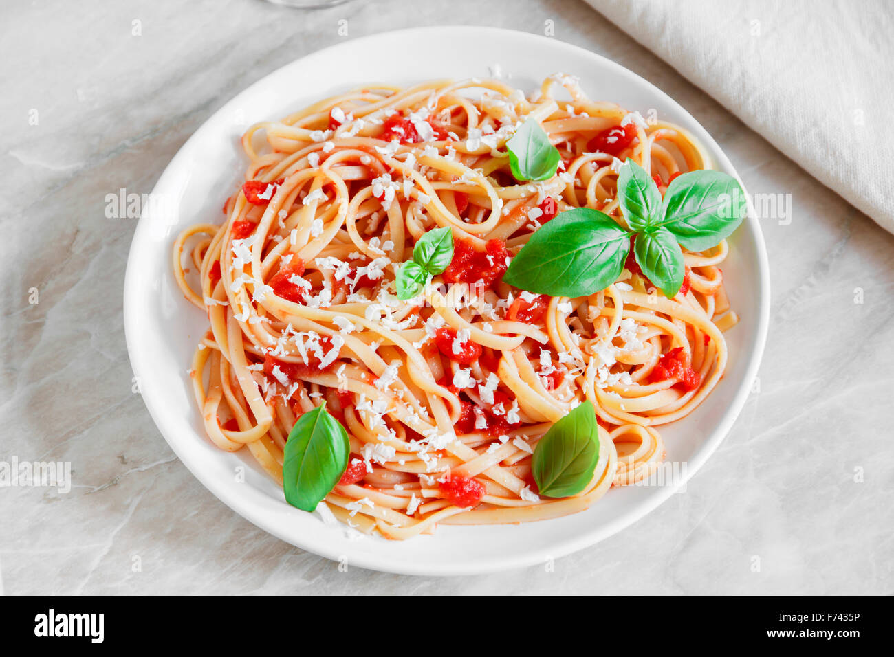 Linguine pasta in tomato sauce and cheese on a plate - Stock Image