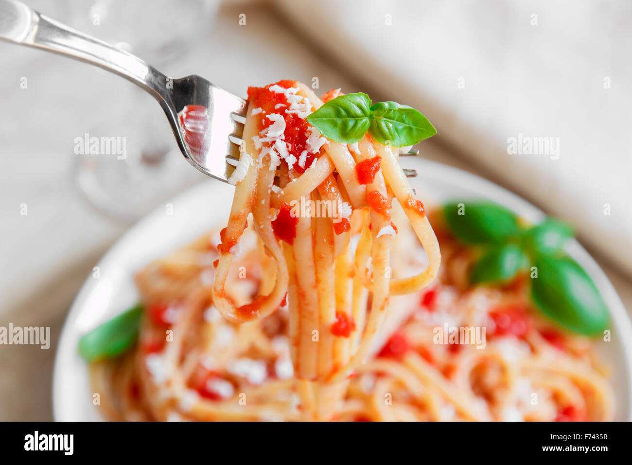linguine pasta with tomato sauce and cheese on a plate - Stock Image