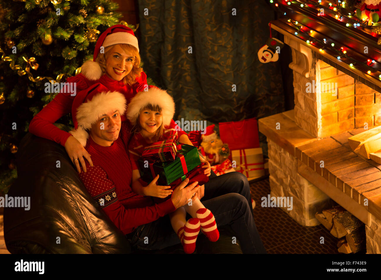 Happy family of three persons in red hats with gifts sitting at Christmas tree near fireplace - Stock Image