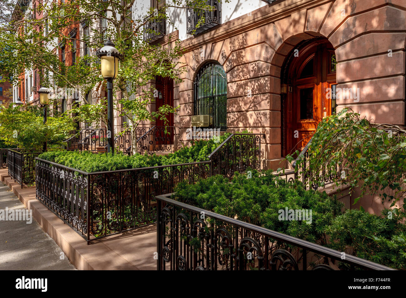 Row of townhouses and their lovely front yards and lampposts. Afternoon light in Chelsea, Manhattan, New York City. Stock Photo