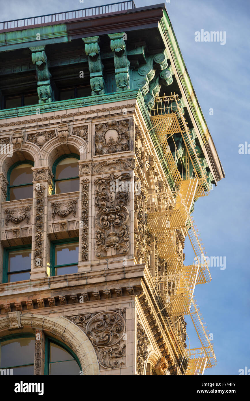 Late 19th century building facade in Soho, Manhattan, New York City. Terra cotta ornaments, copper cornice and fire - Stock Image