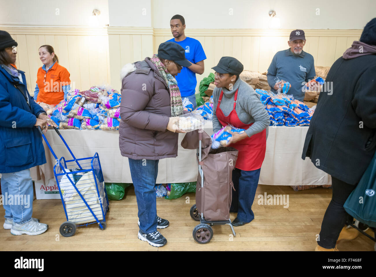 """Volunteers distribute turkeys, stuffing and all the other """"fixin's"""" for a Thanksgiving dinner to the neediest at Stock Photo"""