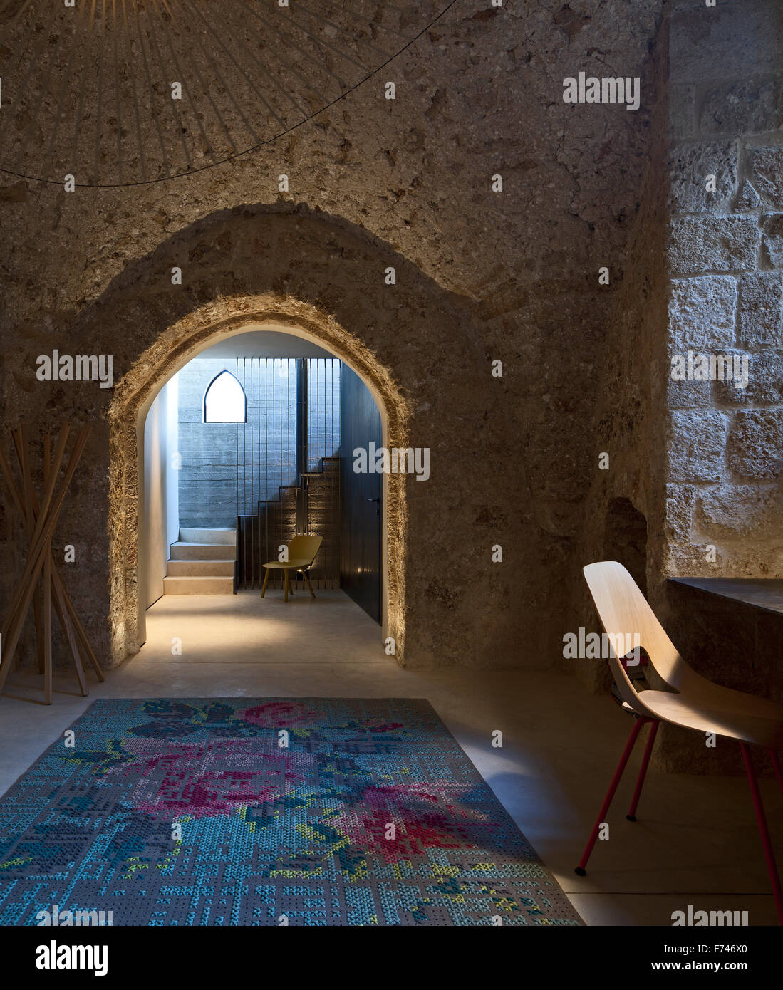 Stone interior arched doorway with floral rug in  House, Jaffa, Tel Aviv, Israel - Stock Image
