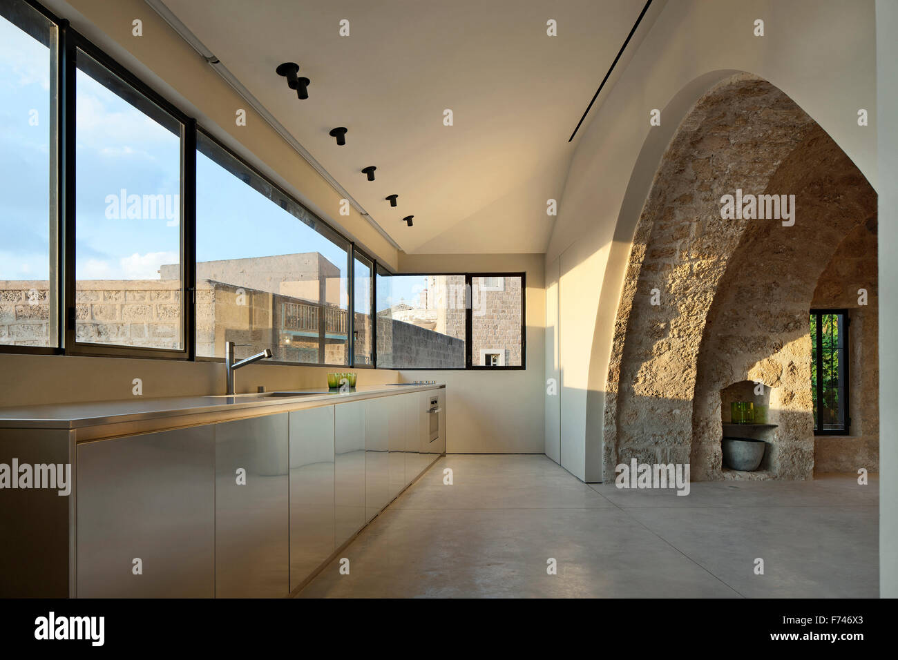 Exposed Stone Arch And Minimalist Kitchen With Uncurtained Windows