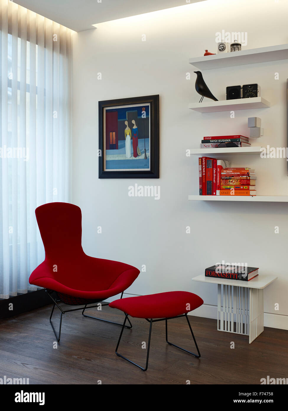 Red armchair and footstool with book shelving in Compass Court Apartment, Shad Thames, London, England, UK - Stock Image