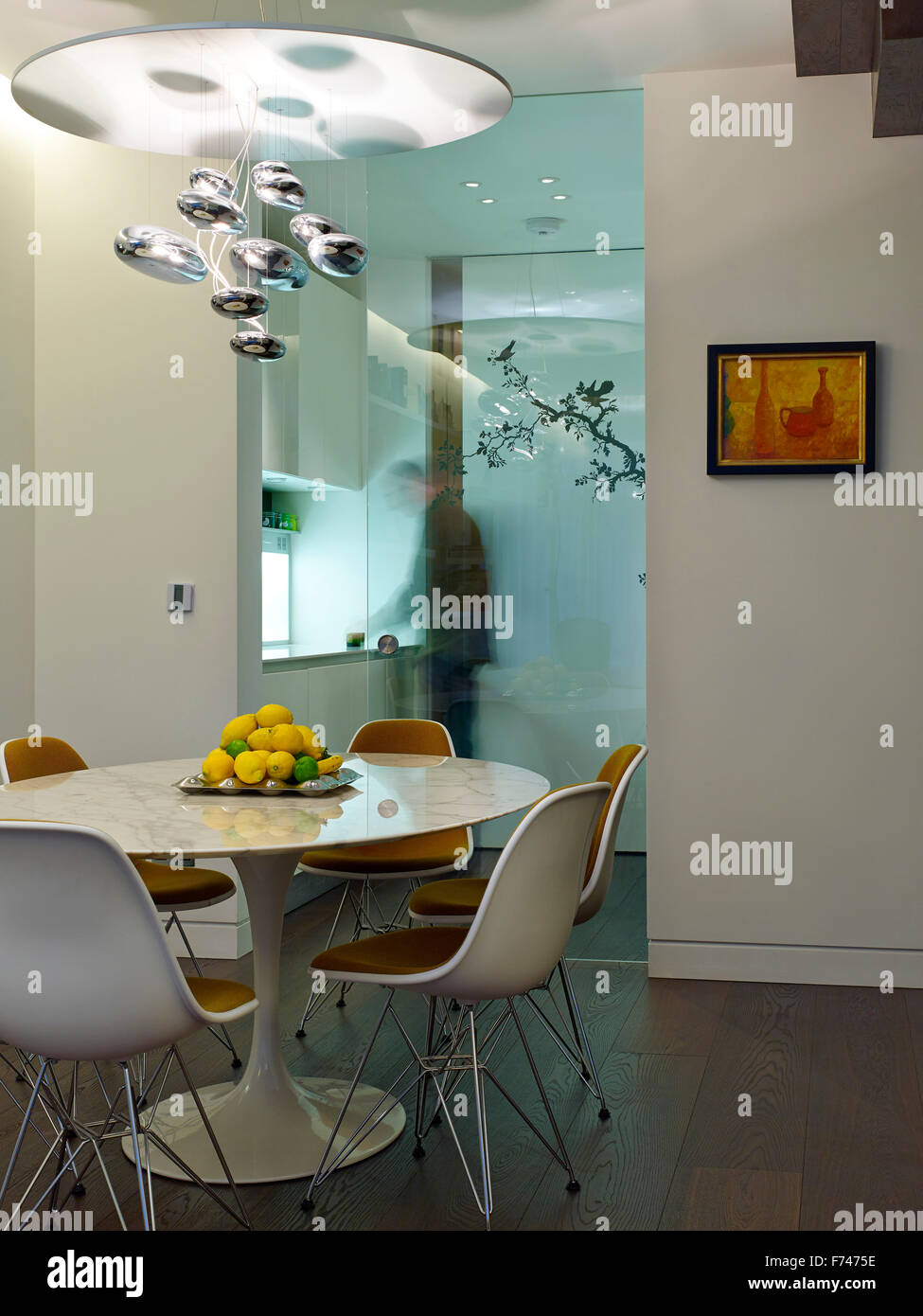 Dining room with glass wall partition in Compass Court Apartment, Shad Thames, London, England, UK - Stock Image
