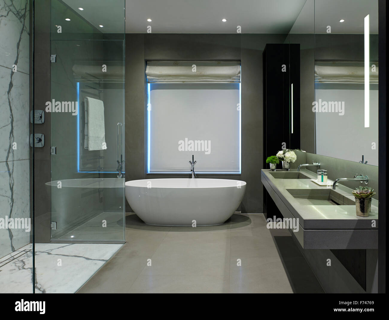 Shower cubicle and bath with double basin in Chelsea Apartment, London, England, UK - Stock Image