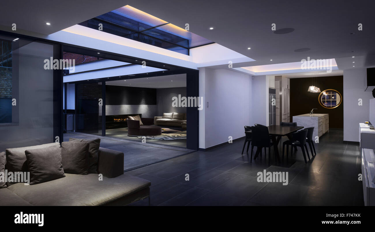 Night shot between the lounges towards the fireplace in Holland Park House by Paul Archer Design, London, England, - Stock Image