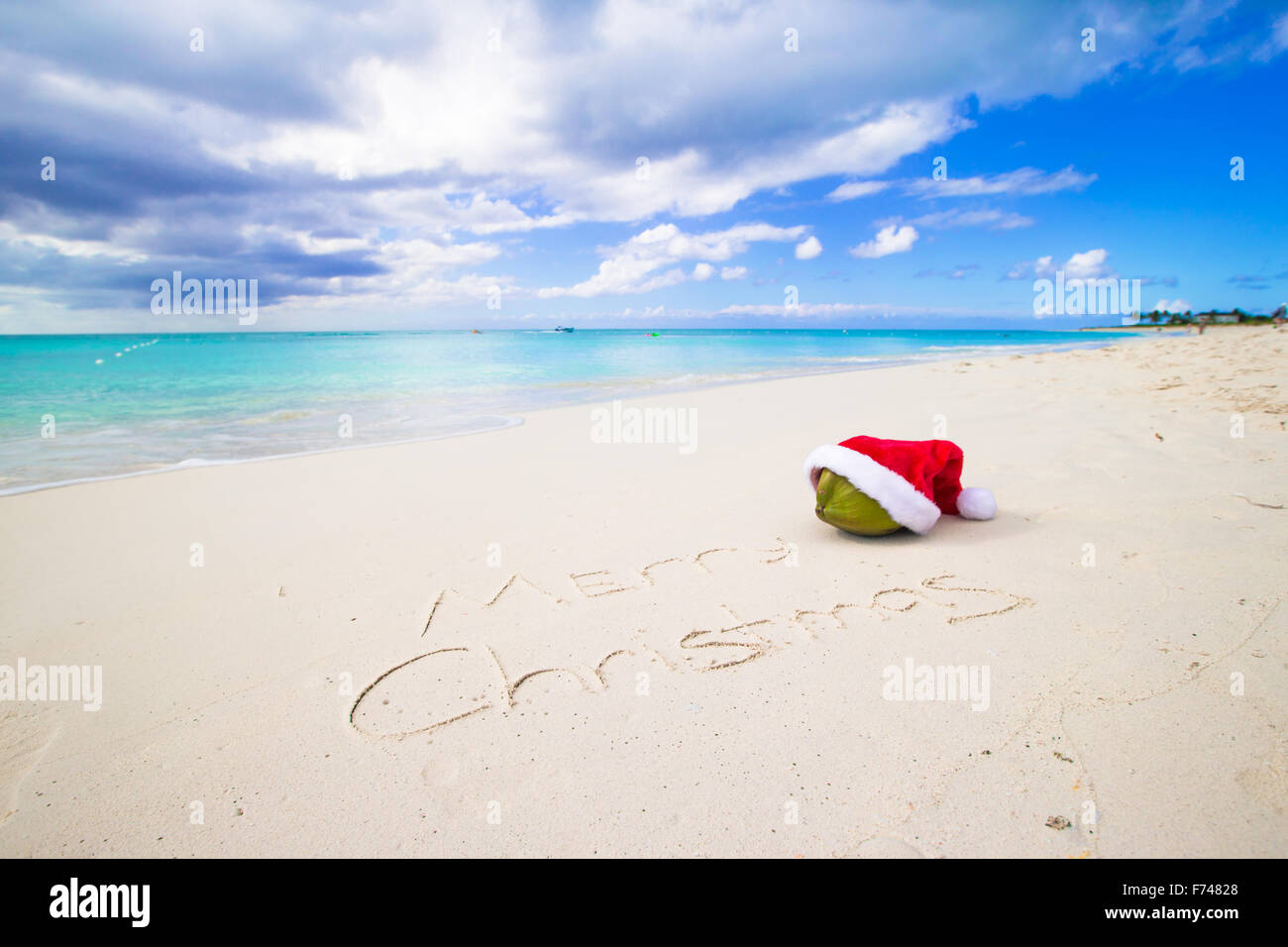 f645c72a5d59e Merry Christmas written on beach white sand with red Santa hat Stock ...