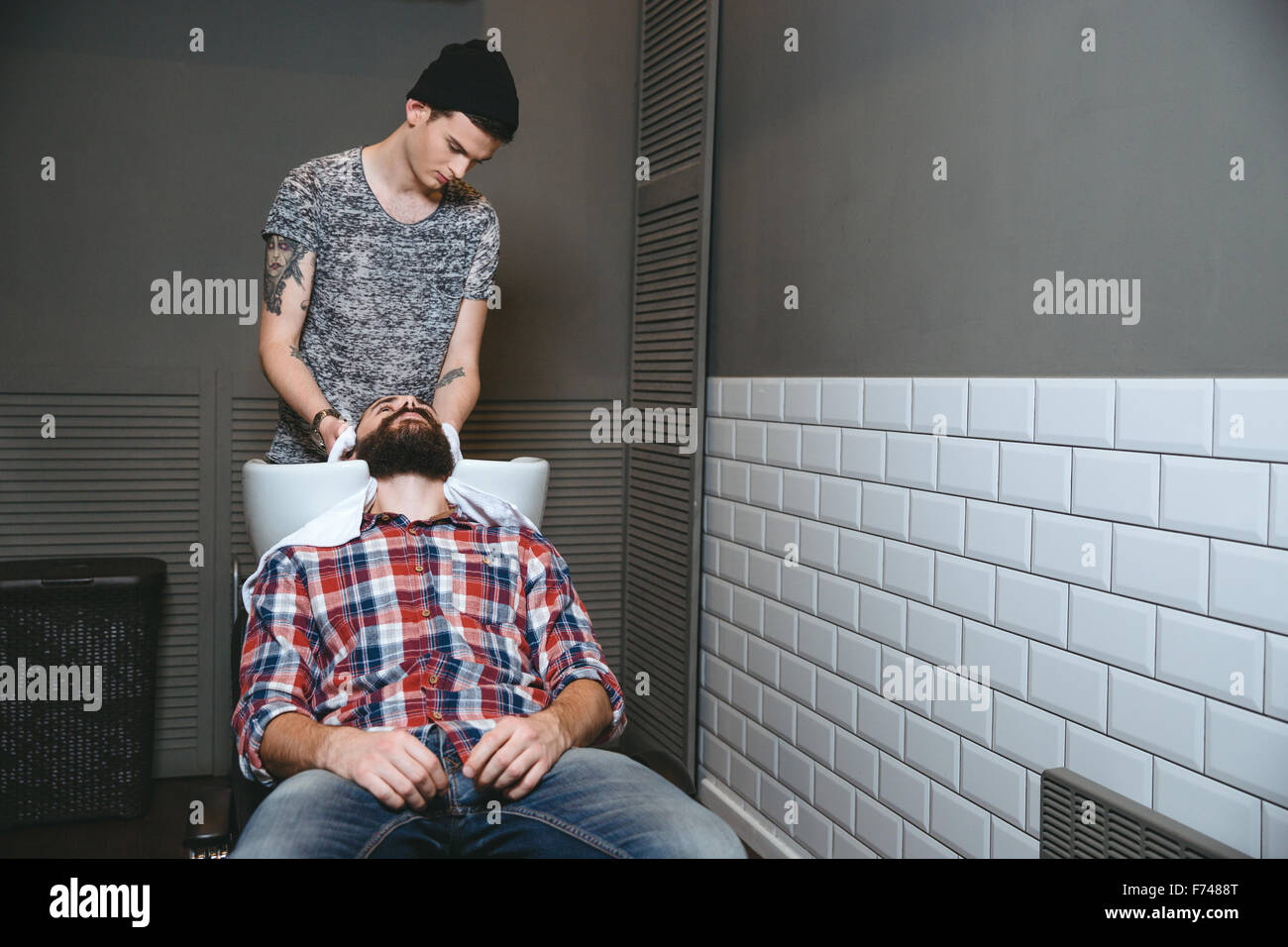 Young handsome barber with tatoo in black hat washing hair of client with beard in plaid shirt and jeans in barbershop - Stock Image