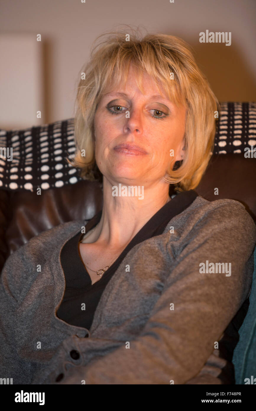 middle aged woman looking concerned - Stock Image