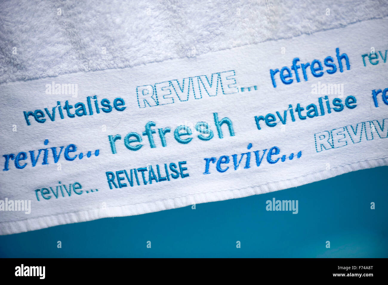 Revive, refresh and revitalise wording on edge of a bath towel. - Stock Image