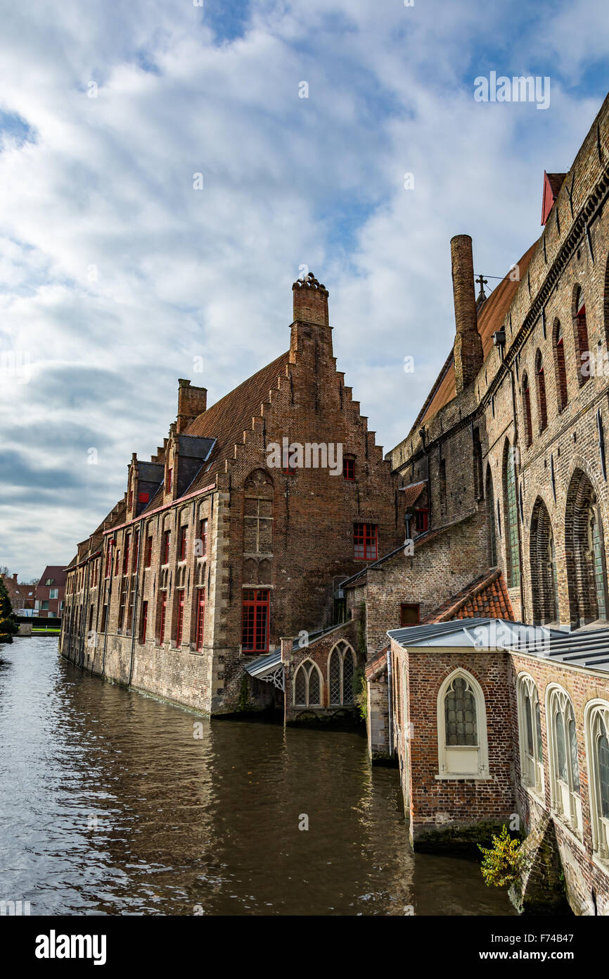 Medieval houses over canals of Bruges on a cloudy day, Begium - Stock Image
