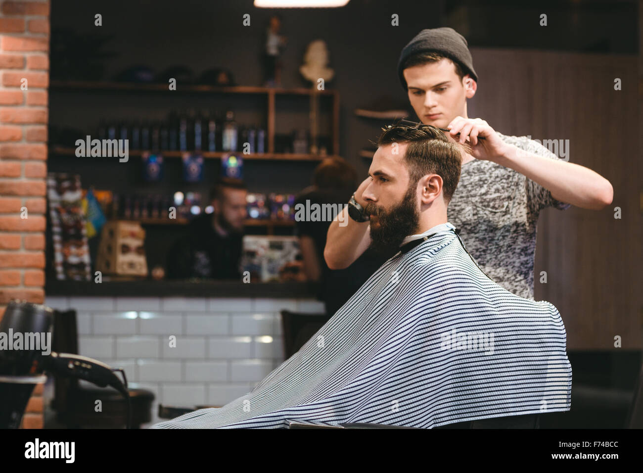 Young handsome barber making haircut of attractive bearded man in barbershop - Stock Image