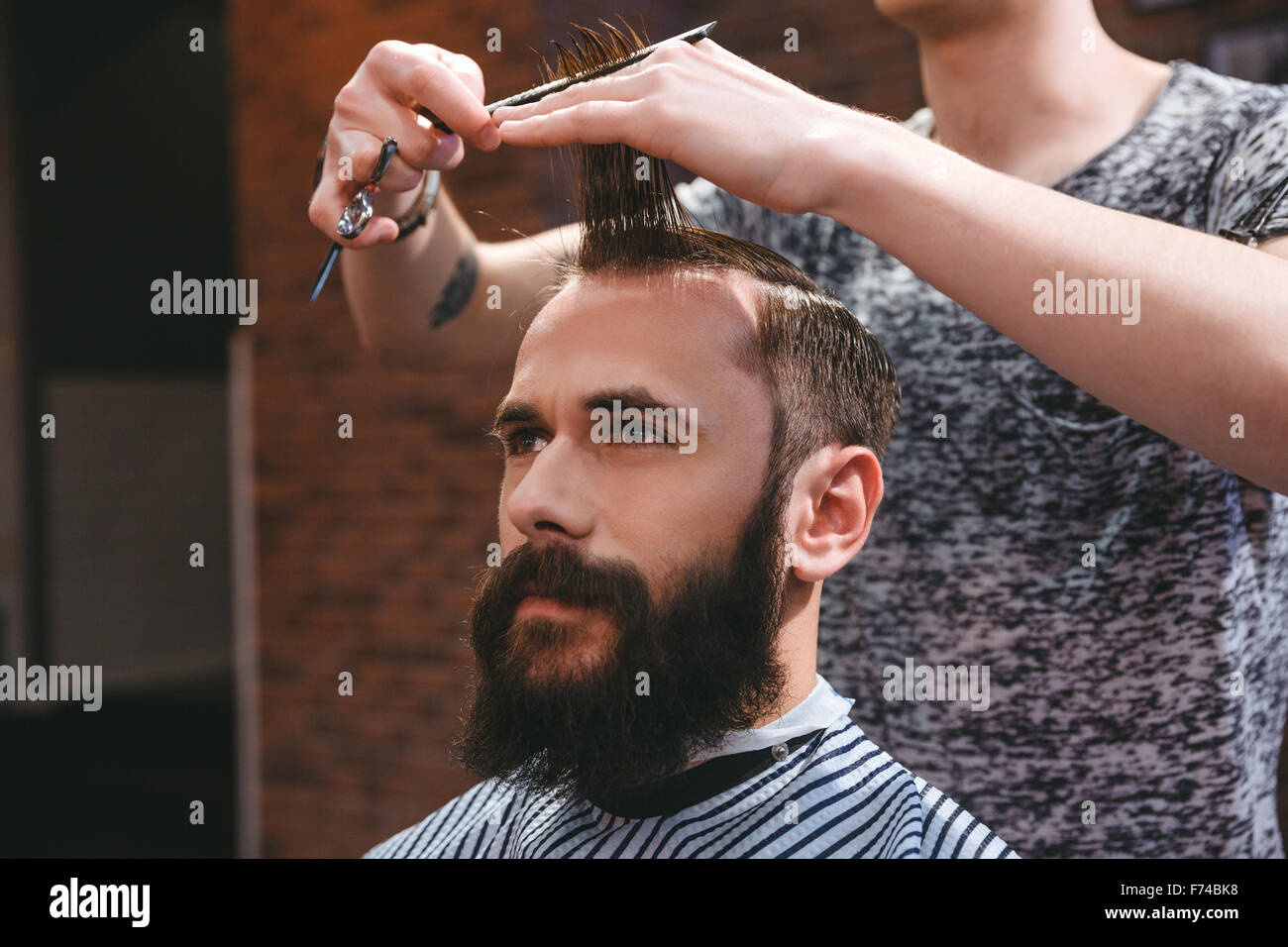 Portrait of young handsome man with beard having a haircut with comb and scissors in hair salon - Stock Image