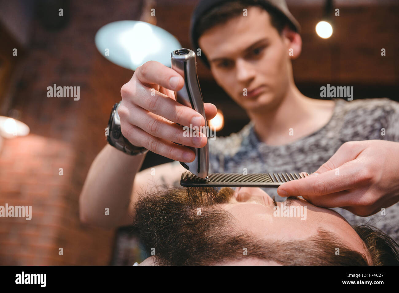 Young concentrated skillful barber making perfect beard to handsome bearded man using trimmer and comb in hair salon - Stock Image