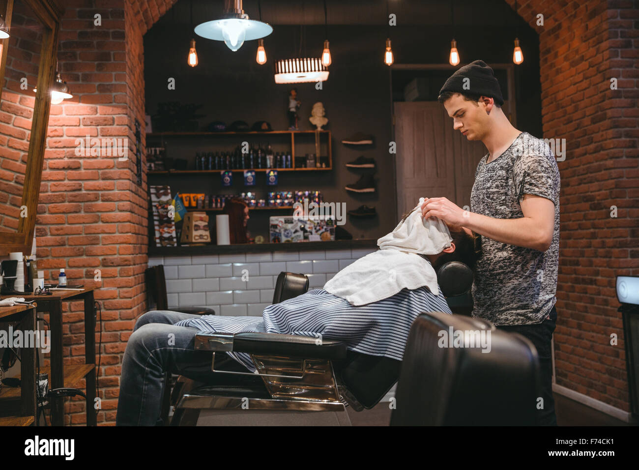 Barber finishing grooming and taking care of client's face in barbershop - Stock Image