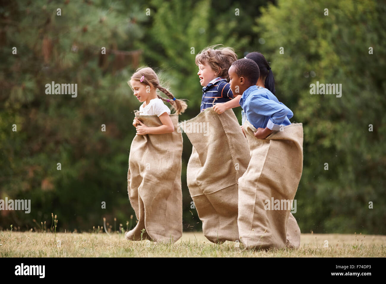 Interracial group of kids competing at a sack race in summer - Stock Image