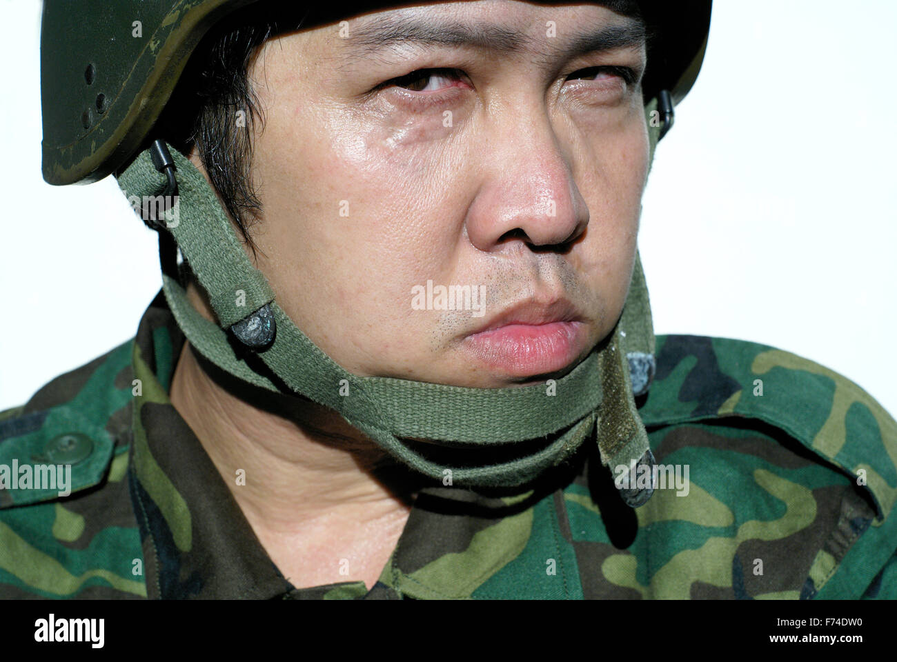 Grim and critical asian soldier with helmet - Stock Image