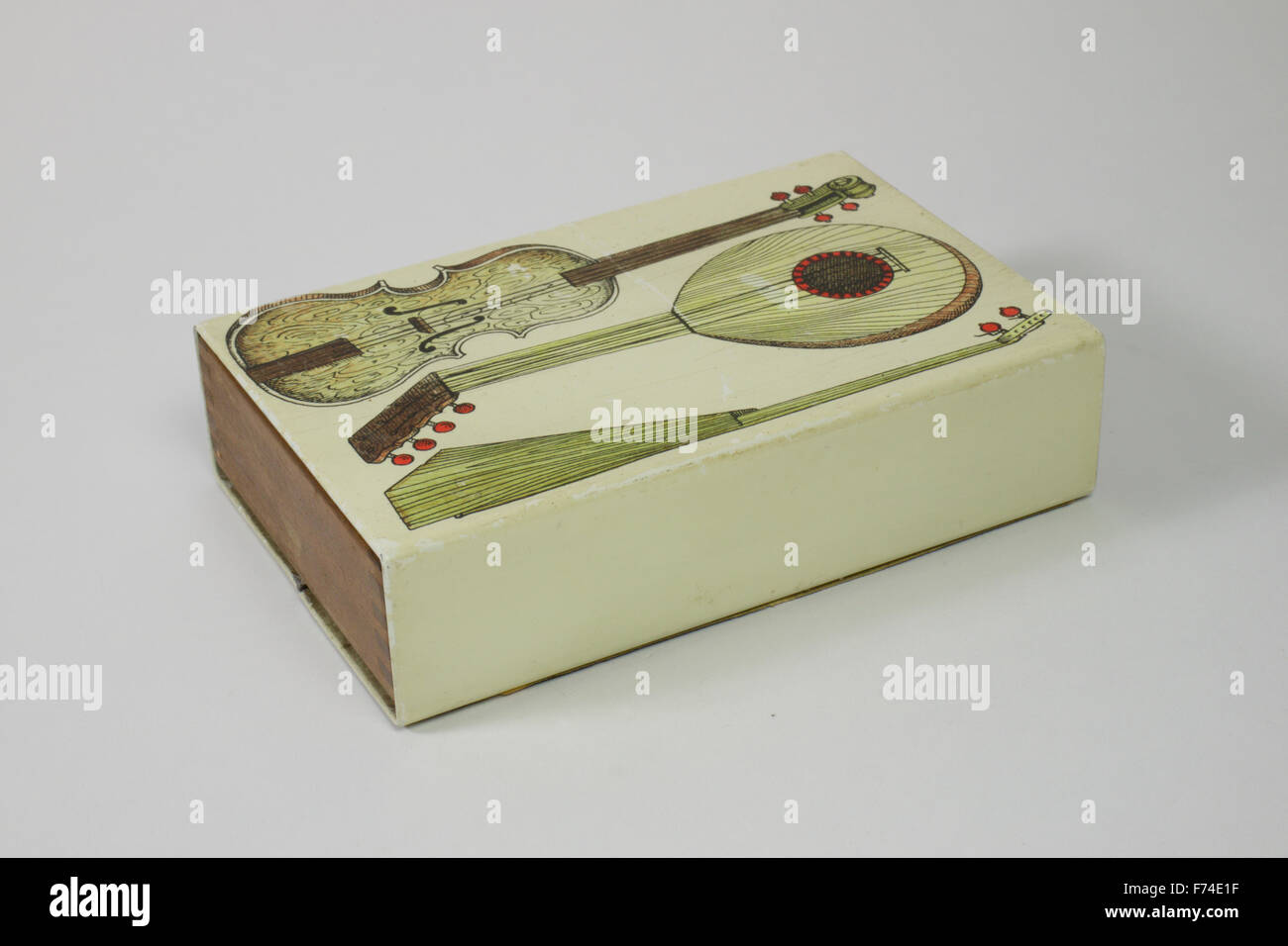 Fornasetti box with sliding mahogany interior, top decorated with three musical instruments. The box measures 14cm - Stock Image