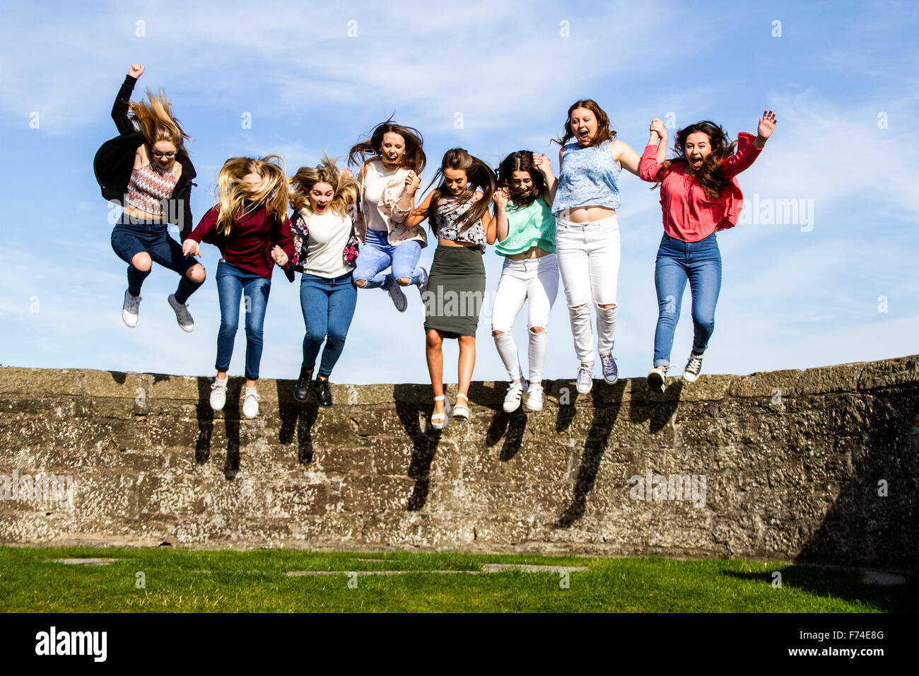 Eight teenage girls holding hands and jumping off the Broughty Ferry Castle wall on a sunny day in Dundee, UK Stock Photo