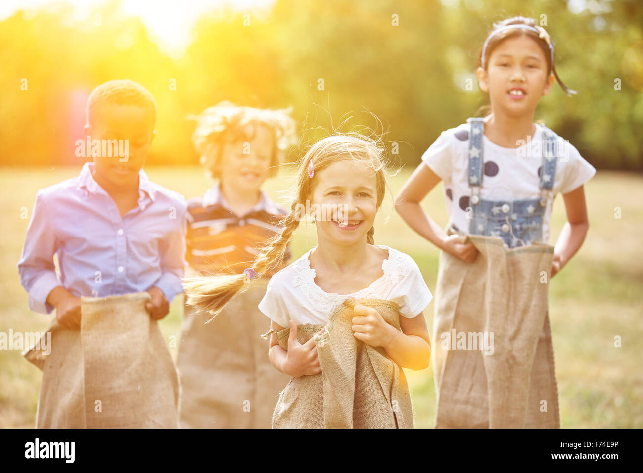 Group of kids at sack race smiling and having fun - Stock Image