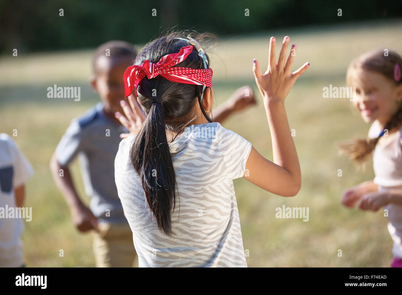 Kids having fun playing blind man's buff at the park - Stock Image