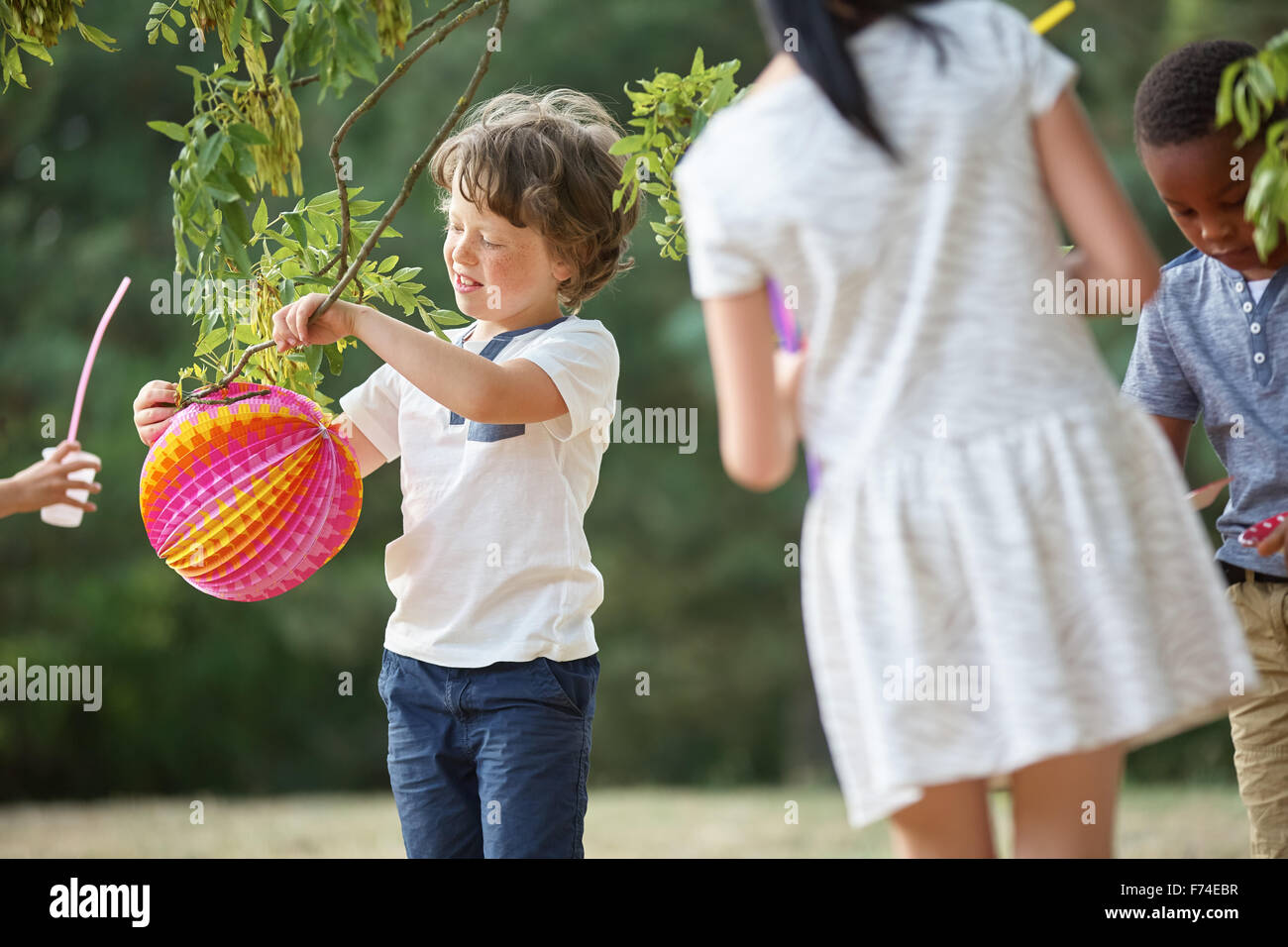 Group of kids at party having fun with lampions - Stock Image