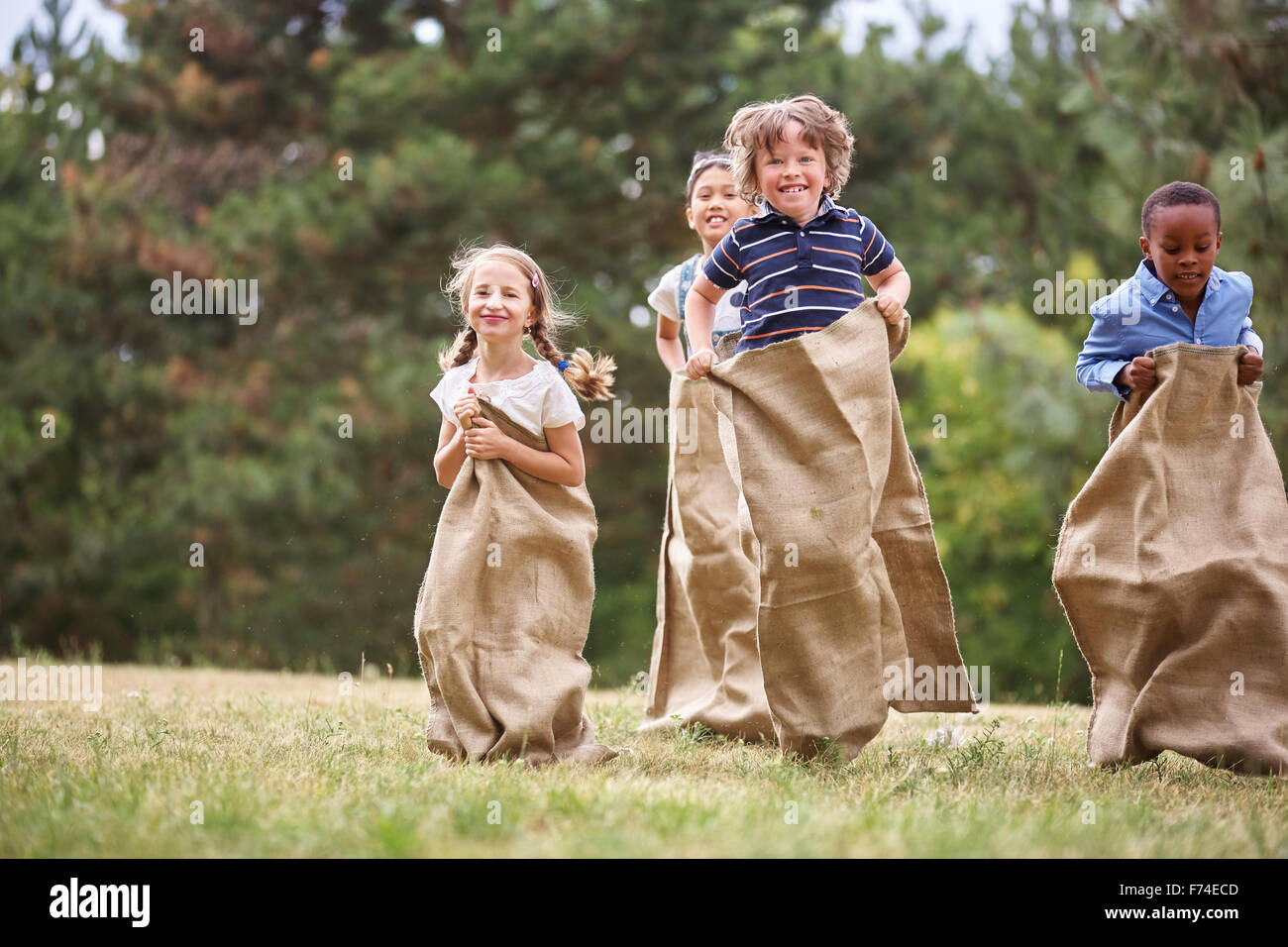 Interracial group of kids having fut at sack race - Stock Image