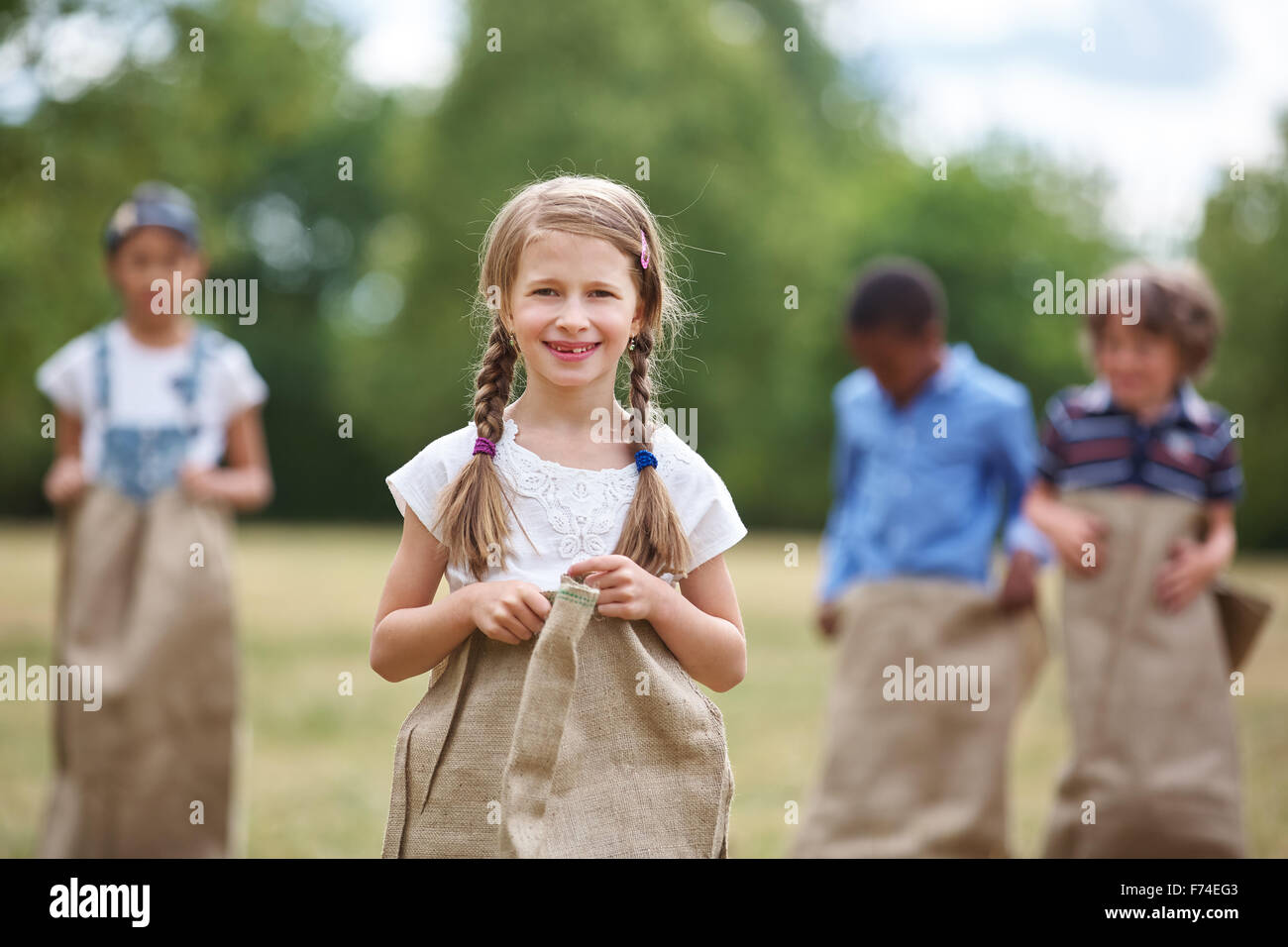 Happy girl with braided hair at sack race smiling - Stock Image
