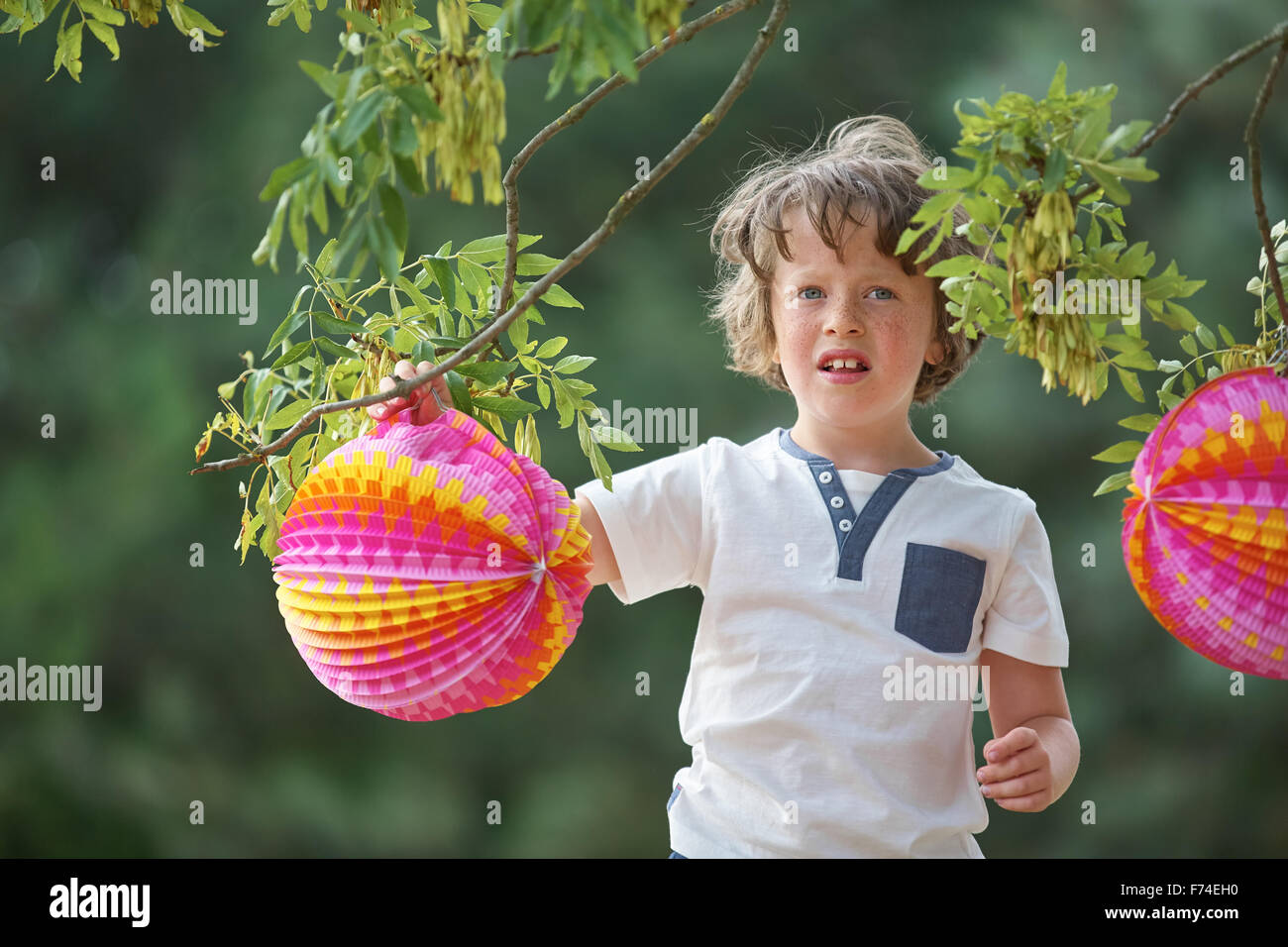 Boy with colorful lampion in summer at a party - Stock Image