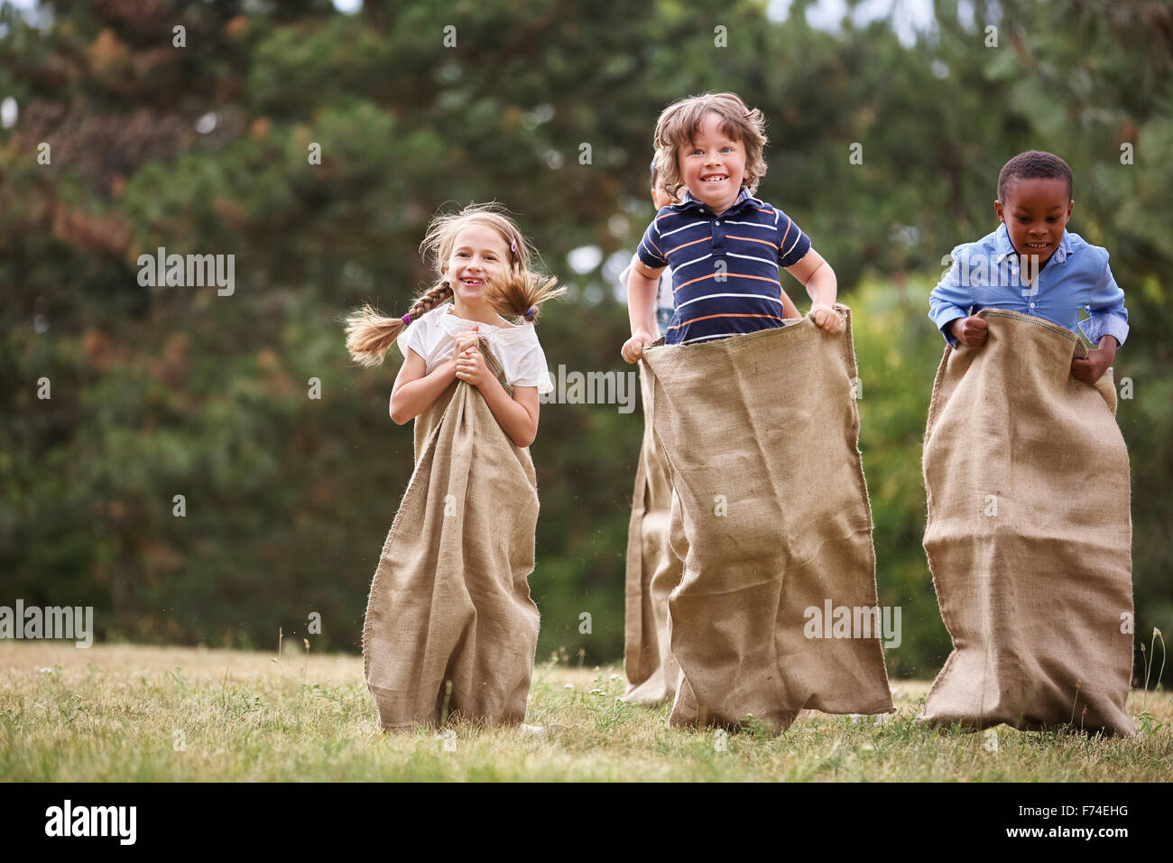 Children competing at sack race and having fun - Stock Image