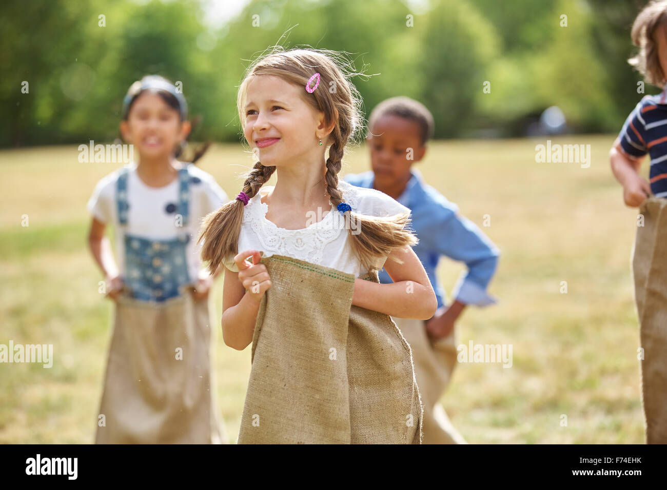 Girl with braided hair at sack race at the park - Stock Image