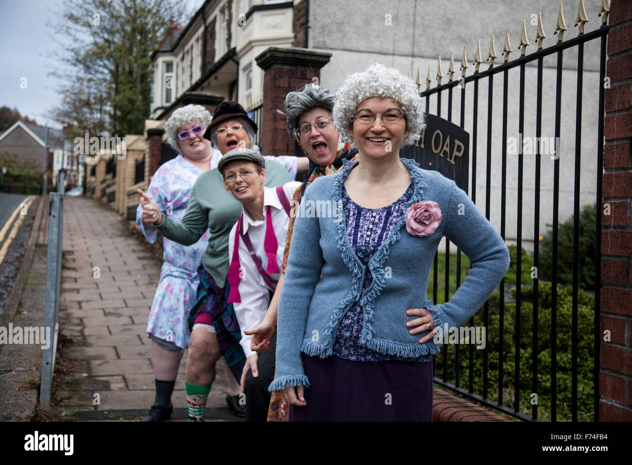 UNITED KINGDOM, WALES; 16 November 2015. Women dressed as old ladies pose in front of OAP Welfare Hall in Llanbradach - Stock Image