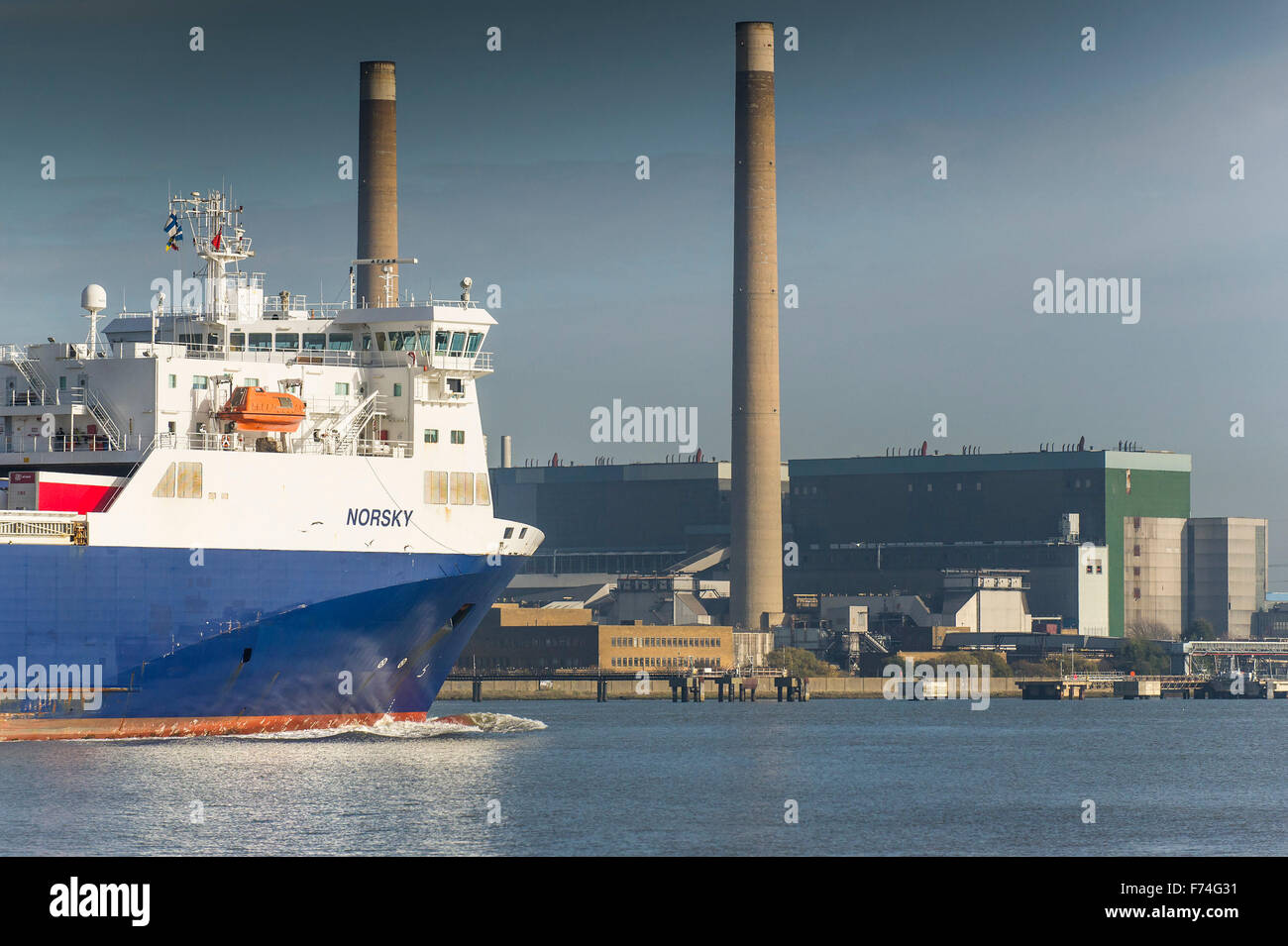 The Ro-Ro cargo ship, Norsky passes Tilbury B Power Station as she steams downriver on the River Thames. - Stock Image