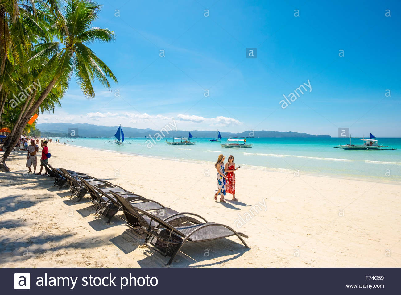 People walking past lounge chairs on on White Beach, Boracay