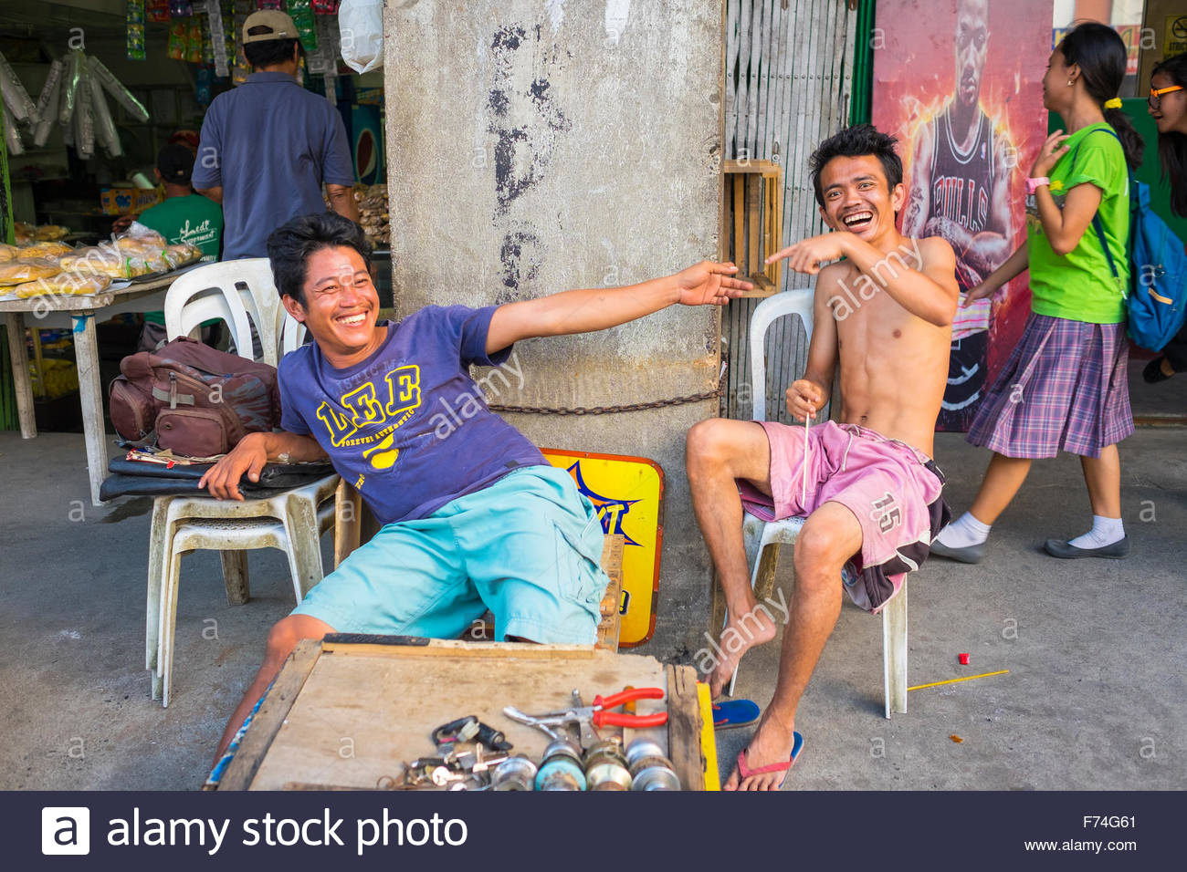 Two young Filipino men laughing and pointing at each other, Central Market, Iloilo City, Western Visayas, Philippines - Stock Image