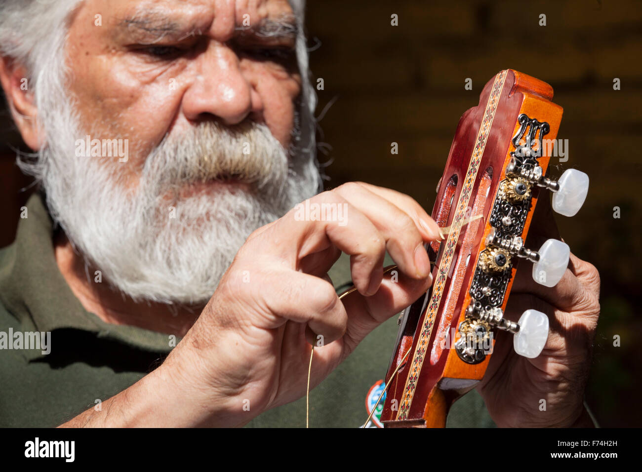Guitar maker Sistos Pasaye strings one of his products outside a shop in Paracho, Michoacan, Mexico. - Stock Image