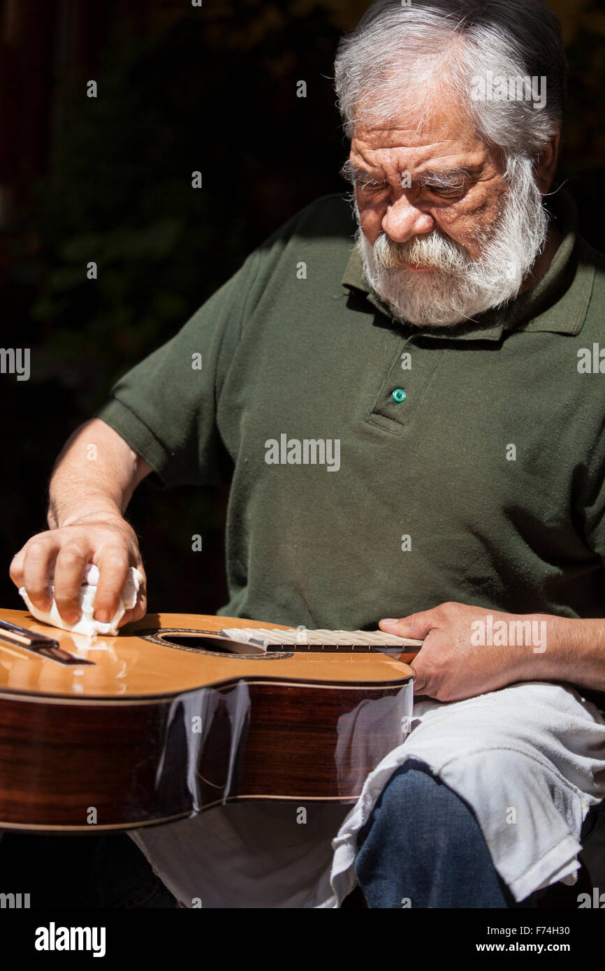 Guitar maker Sistos Pasaye polishes one of his products outside a shop in Paracho, Michoacan, Mexico. - Stock Image