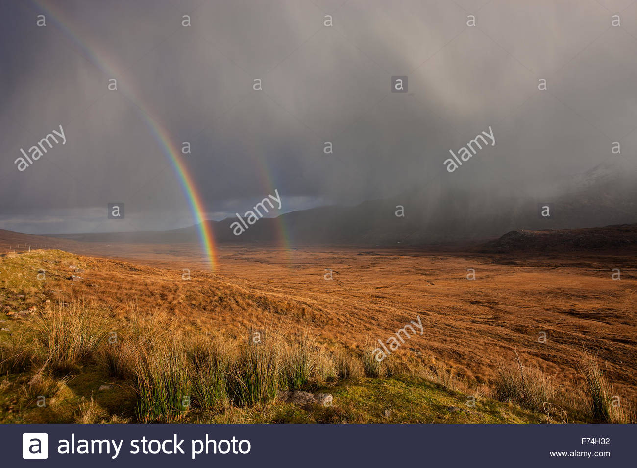 Dramatic light with a double rainbow over moorland near the Kyle of Tongue, Highlands of Scotland. - Stock Image