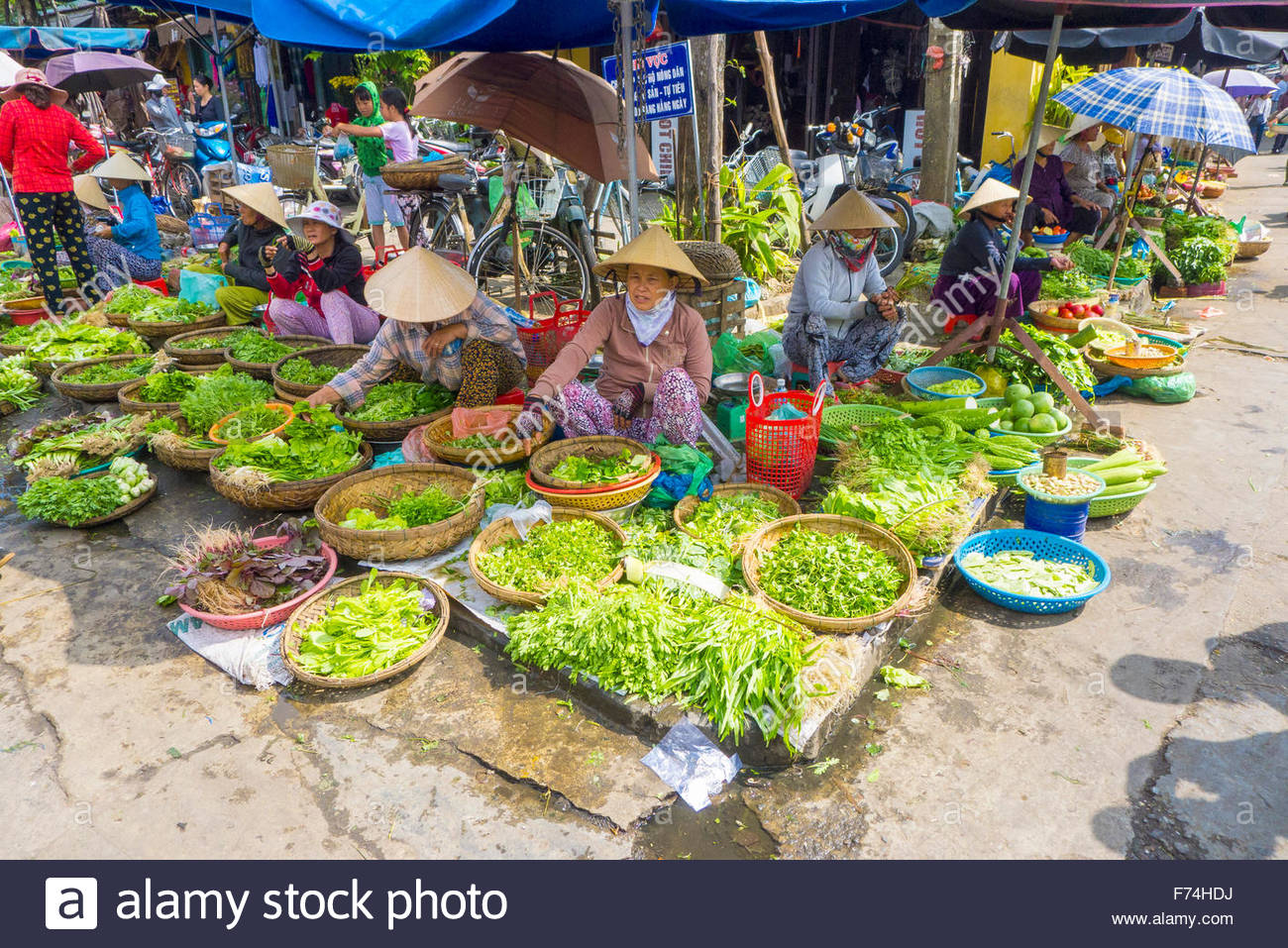 Women selling vegetables at street market, Hoi An, Quang Nam Province, Vietnam - Stock Image