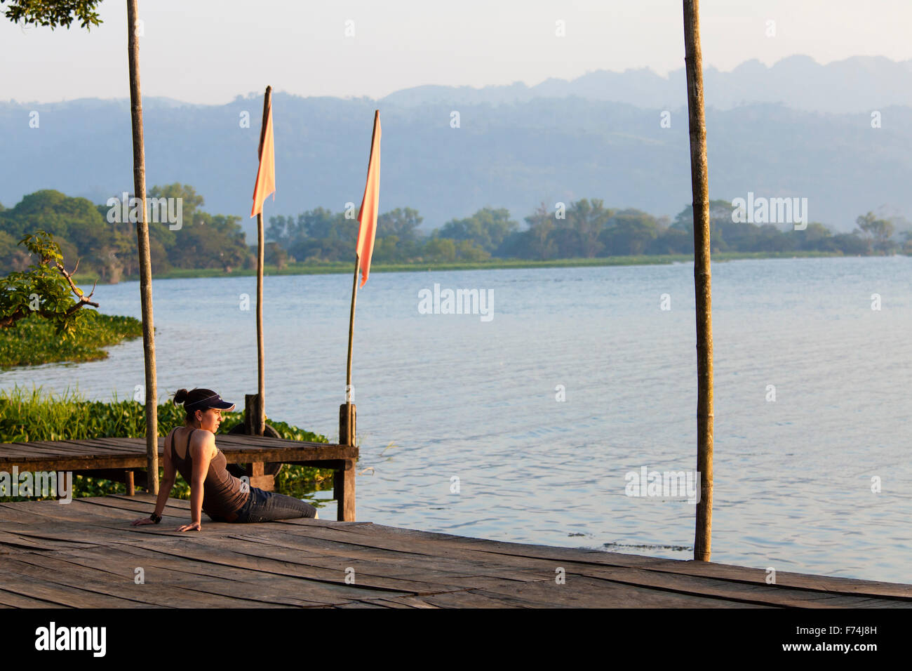 A young woman sits on the docks of Catemaco Lake in Veracruz, Mexico. - Stock Image